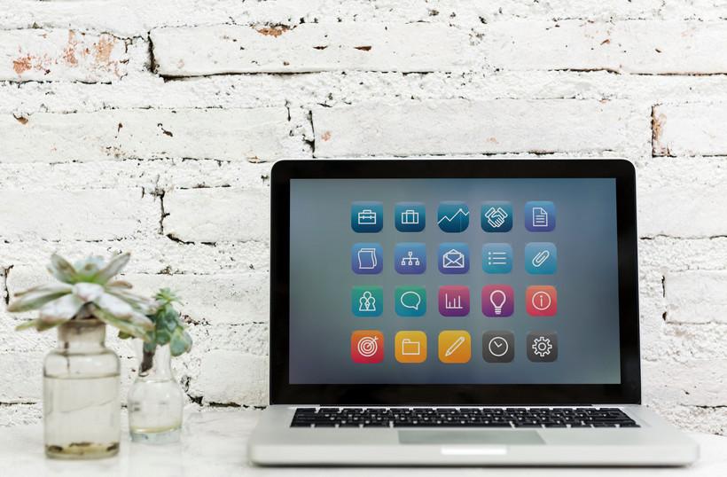 Auf dem Bild ist ein aufgeklappter Laptop vor der weißen Backsteinwand zu sehen. Der Bildschirm zeigt verschiedene bunte Icons mit Werkzeugsymbolen. Links vom Laptop stehen zwei Vasen mit grünen Pflanzen.