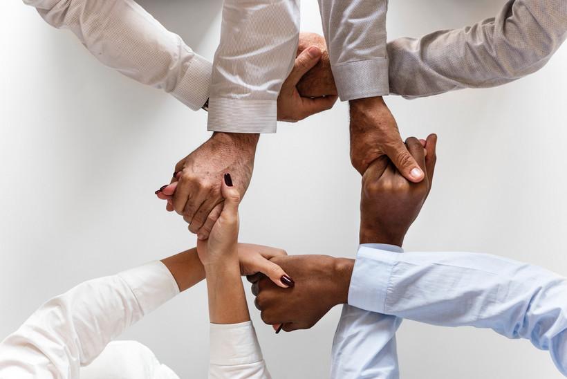 Vier Hände, die sich gegenseitig festhalten.