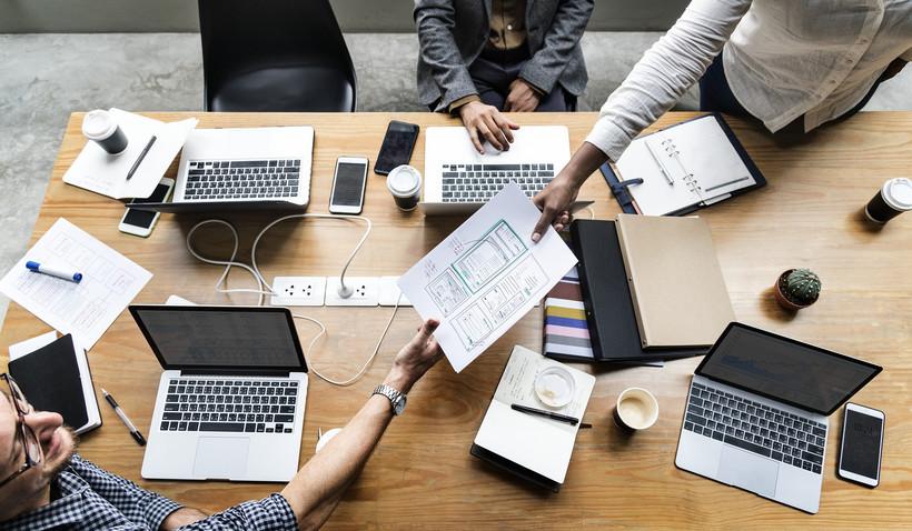 Von oben fotografiert: Ein Schreibtisch, an dem drei Personen an den Laptops arbeiten. Eine Person reicht der anderen gerade ein Dokument über.