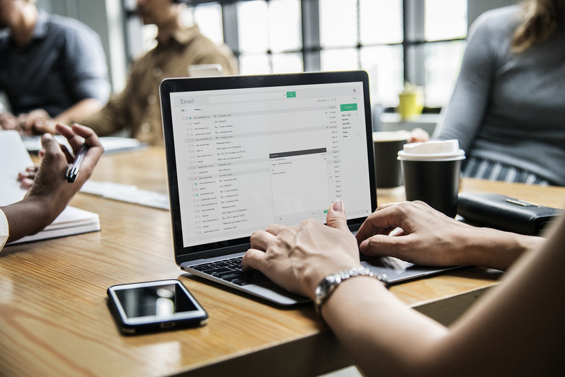 Das Foto zeigt eine am Schreibtisch sitzende und am Laptop arbeitende Frau, wobei man nur ihre Arme sieht. Links von dem Laptop liegt ein Smartphone und rechts davon steht ein Kaffee-Becher. Im Hintergrund befinden sich weitere Personen, die mit am Tisch sitzen.