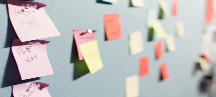 Auf dem Bild ist eine Wand mit farbigen Postings, die zum Prozess des Design Thinkings genutzt werden. Die Posts sind untereinander mit Text beschriftet.