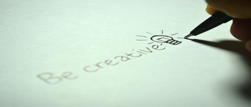 Auf dem Bild ist auf einem türkisen Papier das Wort creative drauf geschrieben mit einer Glühbirne daneben gezeichnet. Jemand hält einen Stift mit der Hand und schreibt gerade diese Worte.