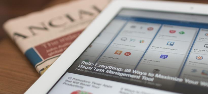 Eine Finanzzeitschrift und ein Tablet, auf dem die Kollaborationsplattform Trello geöffnet ist.