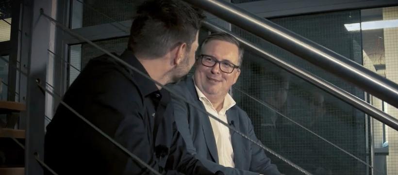 Auf Bild ist Martin Berchtenbreiter mit Sven Zuschlag auf einer Treppe und sie unterhalten sich sitzend