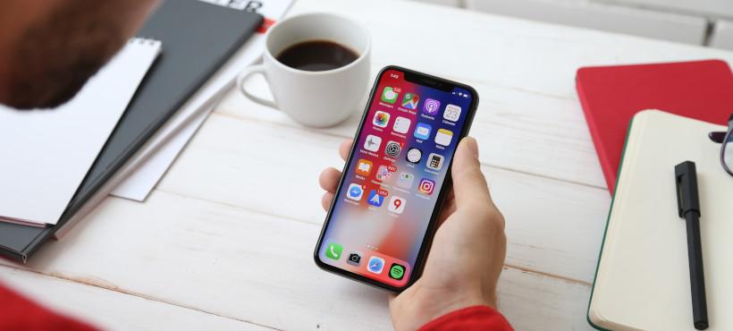 Herr hält Smartphone mit darauf dargestellten Apps