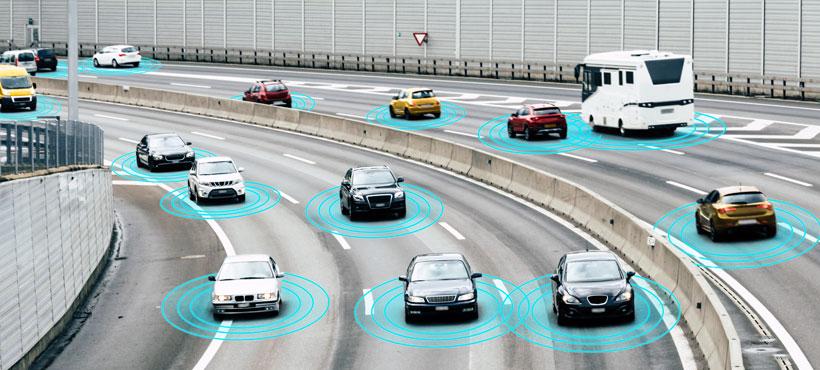 Auf dem Bild erkennt man einen Autoverkehr auf der Autobahn, die Autos senden elektronische Signale und kommunizieren digital miteinander